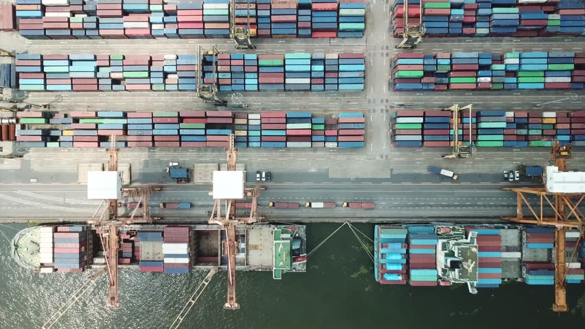 Container ship in export and import business and logistics in Thailand. Shipping cargo to harbor by crane. Water transport International. Aerial view  | Shutterstock HD Video #1011057836