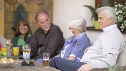 Middle aged friends gathering outdoors and having fun