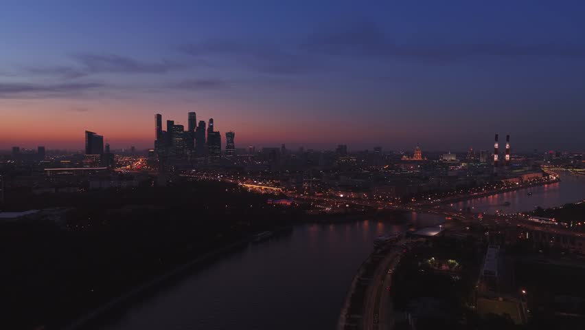 Moscow International Business Center, Moscow-city. Night aerial shot of skyscrapers with city lights and cars on roads and the Moscow river on the background. Aerial high altitude drone flight. UHD 4K | Shutterstock HD Video #1011088196