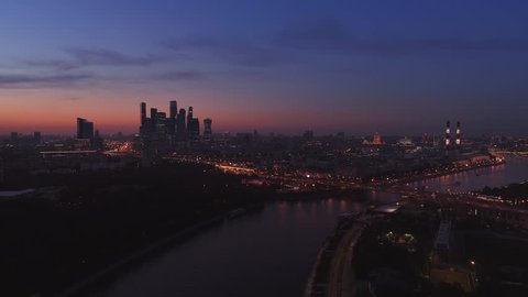 Moscow International Business Center, Moscow-city. Night aerial shot of skyscrapers with city lights and cars on roads and the Moscow river on the background. Aerial high altitude drone flight. UHD 4K