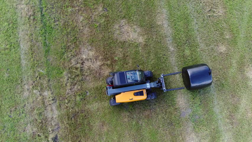Aerial top down view of wrapped silage bale pickup by forklift truck this food is fermented high moisture stored fodder which can be fed to cattle sheep and other such ruminants cud-chewing animals 4k