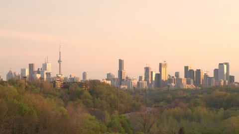 Toronto, Ontario/Canada - May 15, 2018: City panoramic skyline including landmark buildings in downtown core and midtown at dusk, Don Valley Parkway with moving cars visible through green trees