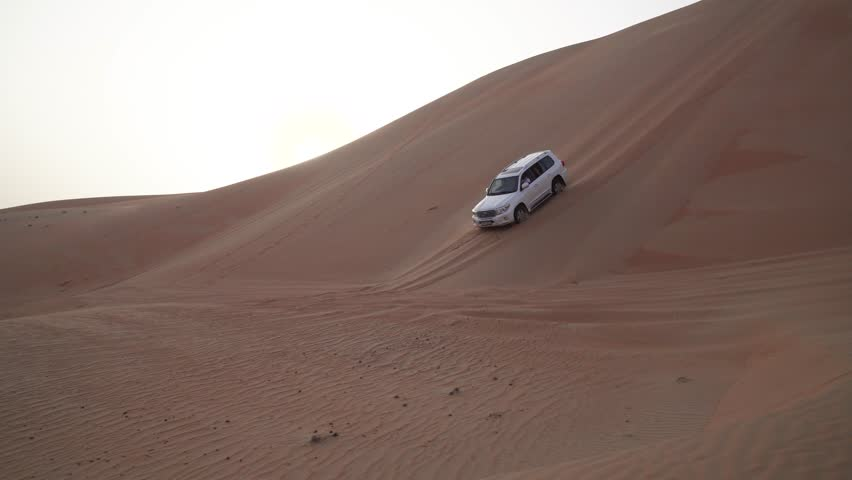 Abu Dhabi, UAE - April 05, 2018: SUV descends from a high dune in the Rub al Khali desert stock footage video #1011114356