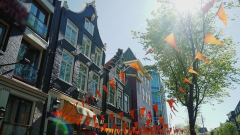 Amesterdam, Netherlands, May 2018: Walking in the streets of Amsterdam. Old houses and triangular orange flags at the top. Steadicam pov video, low angle shot