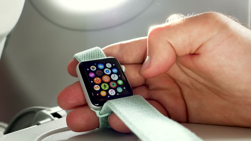 USA - CIRCA 2018: Man hand using Apple Watch made by Apple computers in the business class near the window of a modern plane. Selecting the new app | Shutterstock HD Video #1011148856