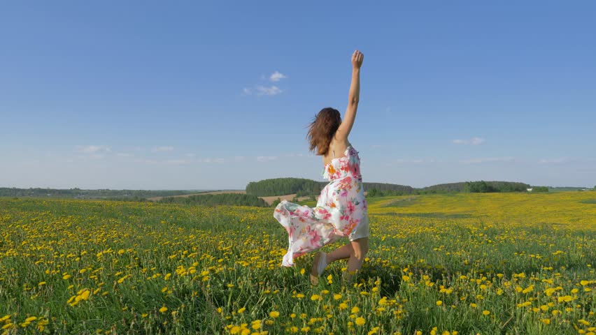 Happy caucasian woman in a beautiful dress dancing with pleasure in a blooming yellow field. Turning around in place, smiling and holding the edges of the dress. Slow motion, 4k, 3840x2160