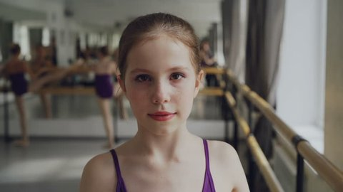 Portrait of young girl starting ballet-dancer with make-up looking at camera and smiling during ballet class in spacious light dancehall. Art and childhood concept.