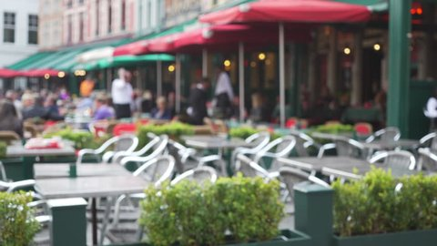 Out of focus background plate of row of European cafe patios for compositing. Defocused video backdrop of tables and chairs outside coffee shop for green screen. 4k