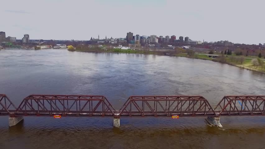 Drone tracks over the Prince of Whales bridge in Ottawa. Parliament and city skyline in the background.