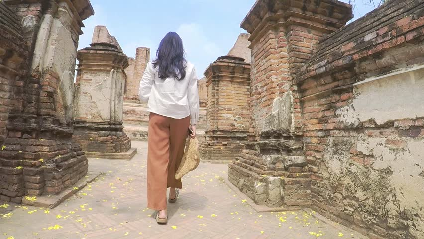 The camera follows a women walk to temples at Ayutthaya, Thailand.
