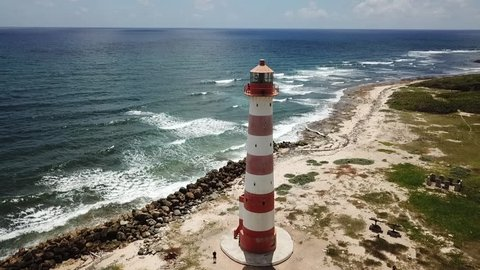 Zoom out areal video of red and white lighthouse in the Caribbean, Jamaica
