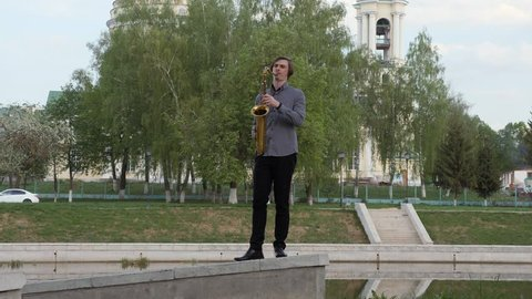 young man plays the saxophone. The musician plays on the wind instrument, walks the parapet to the camera, the camera is in motion. Man moves on the narrow road. man on the background of the city