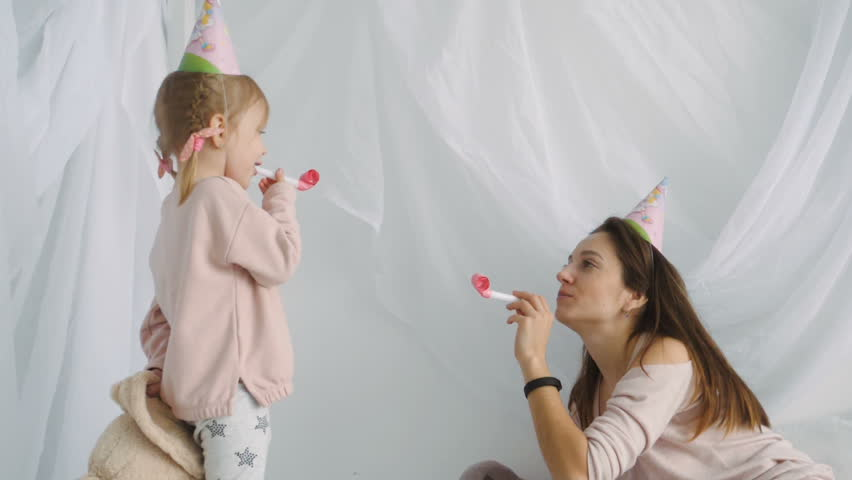Slow motion shot of little cutey girl and her beautiful mother wearing festive cap and blows horn