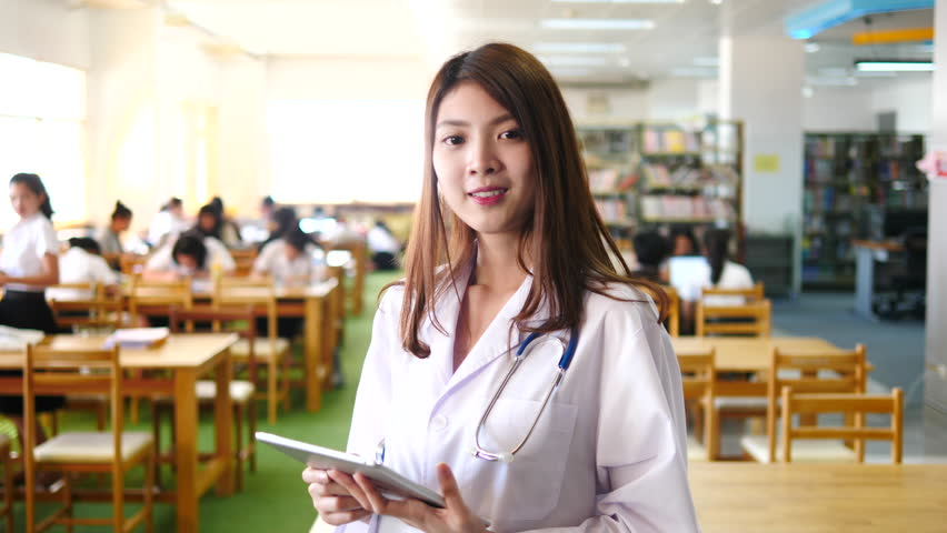 Advertising, Education, Business, Medical, Technology Concept - Asian medical student with digital tablet. Attractive young female doctor in white coat and smiling while standing in library. | Shutterstock HD Video #1011267176