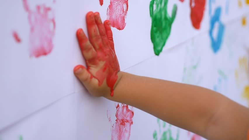 Close up of little cute child's hands making colorful handprints on the white wall in slow motion 50fps