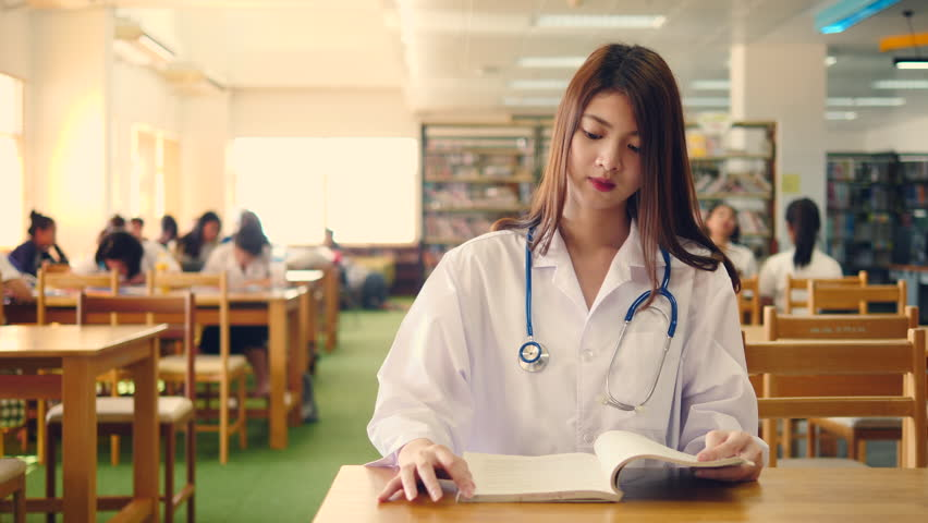 Advertising, Education, Business, Healthcare and Medical Concept - Beautiful young asian medical students with attractive smile and stethoscope looking at camera and  reading book in library. | Shutterstock HD Video #1011276746