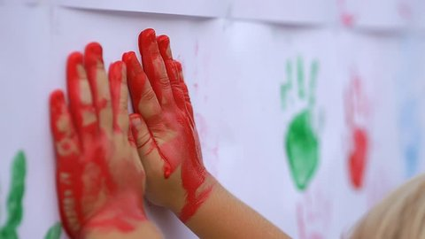Close up of little cute child's hands making color handprints on the white wall in slow motion 50fps