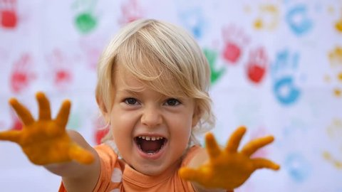 A little cute happy child scaring by hands in colorful print and smiling on color handprints background in slow motion 50fps