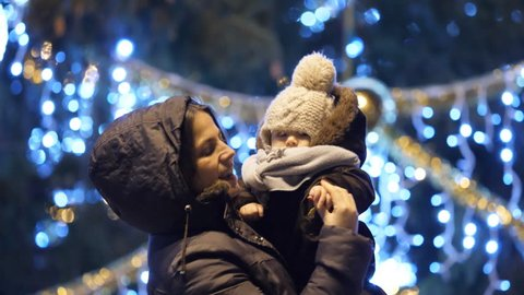 Young mother and adorable baby dancing in front of Christmas tree outdoor