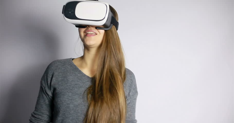technology, virtual reality, entertainment and people concept - happy young woman with virtual reality headset or 3d glasses. Woman with virtual reality goggles. Studio shot, gray background