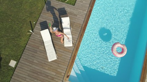 AERIAL, POV: Young woman relaxing by the pool starts throwing things at drone flying above her. Annoyed female neighbor jumps around her pool trying to stop drone taking photos of her sun tanning.