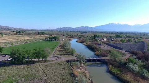 Aerial view over a river and bridge with a park and farms in this rural setting and mountains in the distance