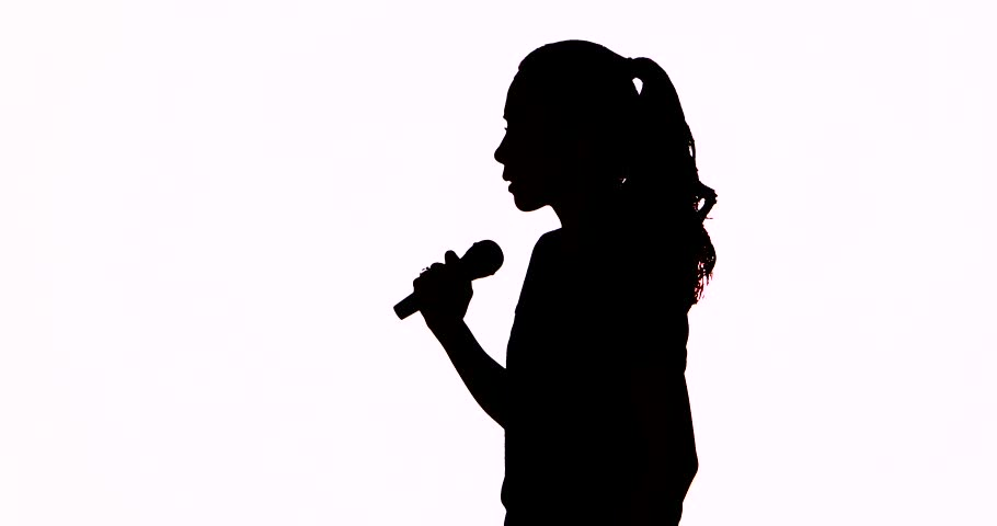 Silhouette of a young woman singing with a microphone in the studio, isolated on white background. Shot in 4k resolution | Shutterstock HD Video #1011312236