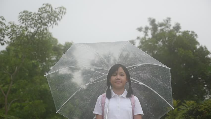 Beautiful Asian girl walking with umbrella on rainy day | Shutterstock HD Video #1011315056