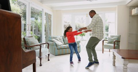 Father and daughter dancing in kitchen at home
