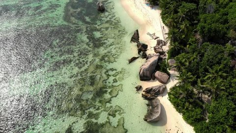 Seychelles tropical island luxury vacation, drone view at the tropical beach with palm trees and white sand blue ocean of La Digue Seychelles