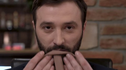 Closeup of a bearded man's face wiping his mouth with a napkin in a fine dining restaurant.
