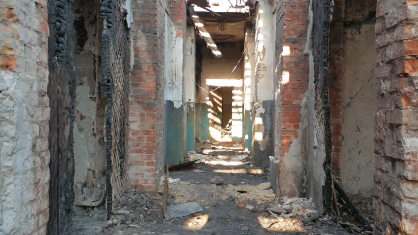 First person view of moving forward in corridor of ruined abandoned building after disaster, fire, war or hurricane, demolition apocalypse concept.   Shutterstock HD Video #1011346256