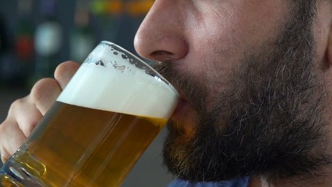 Close up of male face drinking beer in cafe, super slow motion 240fps