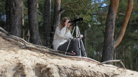 Attractive woman looks through a telescope in a forest on the river bank 4k