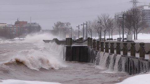 Huge powerful waves breaking at seawall in major severe storm in hurricane force winds