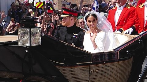WINDSOR, ENGLAND - MAY 19 2018: Slow motion footage of Prince Harry and Meghan Markle wave hands ride in Ascot Landau after their wedding ceremony at St. George's Chapel in Windsor Castle ProRes 4444