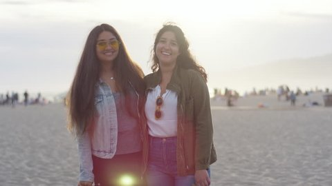 f253dd97ce Portrait Of Girlfriends With Their Arms Around Each Other, Smiling At  Sunset On The Beach