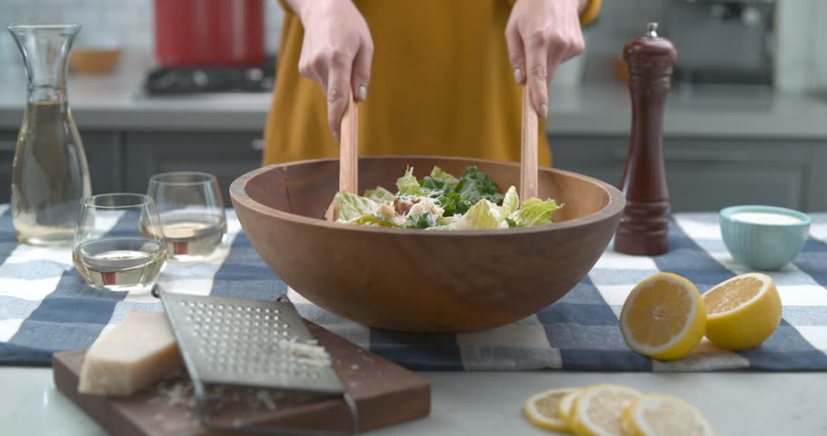 Tossing a bowl of caesar salad in slow motion. Kitchen cinematic scene. Shot with Phantom Flex.