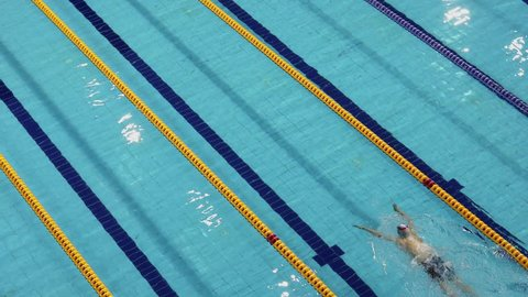 Sportsman swims breaststroke by basin track during competition