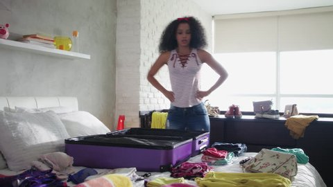 Excited young black woman packing bags for holidays, pretty hispanic girl preparing suitcase for vacations getting ready for travel