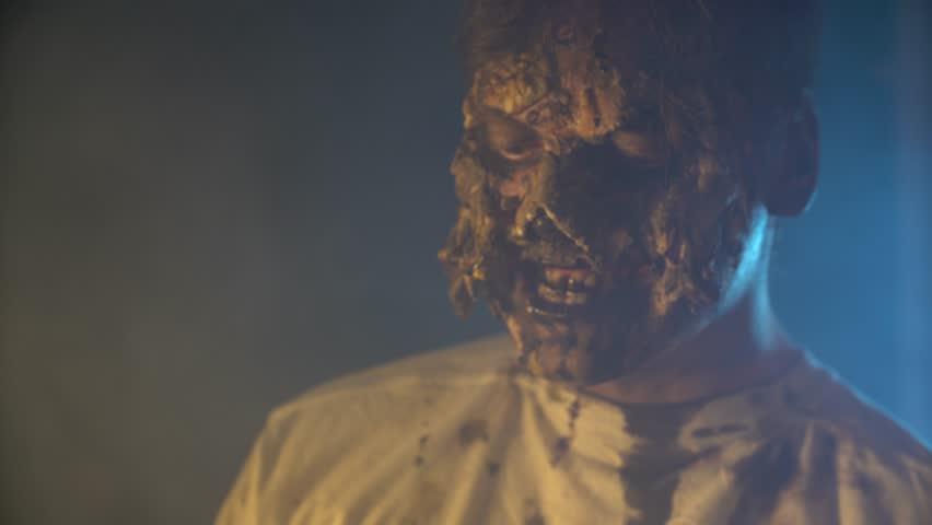 Scary zombie closeup on dark background in Halloween makeup | Shutterstock HD Video #1011440096