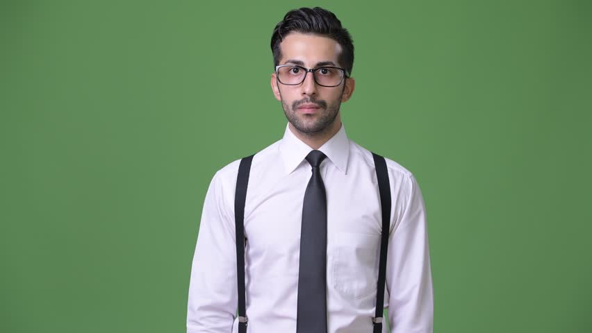 Young handsome bearded Persian businessman against green background | Shutterstock HD Video #1011456926