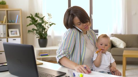 multi-tasking, freelance and motherhood concept - working mother with baby boy at home office calling on smartphone