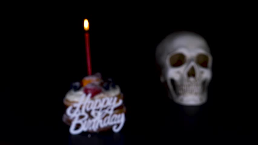 Cake and skull in a festive cap on a black background. 4k, dolly shot, defocusing, blur. | Shutterstock HD Video #1011463256
