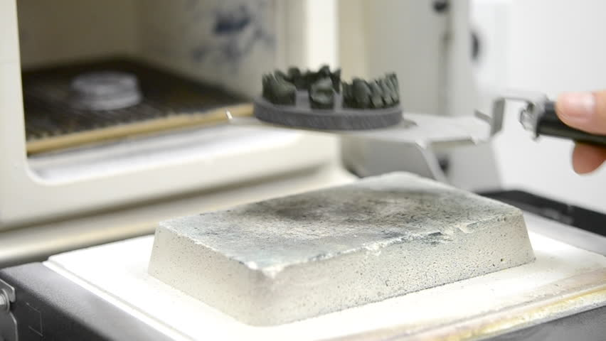 The object created on the 3d printer for metal from metallic powder is placed in furnace for heat treatment synterization. Dental crowns created in laser sintering machine. DMLS, SLM, SLS technology. | Shutterstock HD Video #1011482066