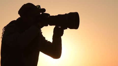 Nature Photographer Taking Pictures at the Sunset. Panoramic Photo. Slow Motion Footage