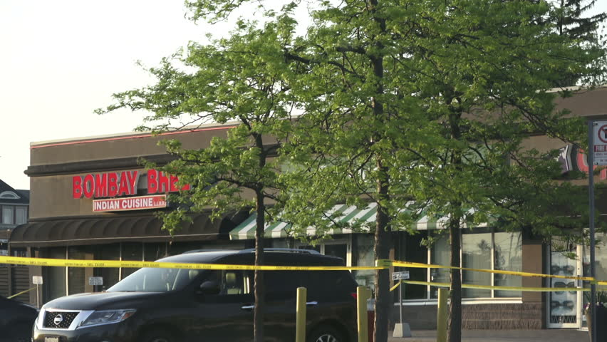 MISSISSAUGA CANADA - MAY 25, 2018: Yellow police tape corded part of a plaza in Mississauga where two masked men entered the Bombay Bhel restaurant and detonated an improvised explosive device | Shutterstock HD Video #1011507386