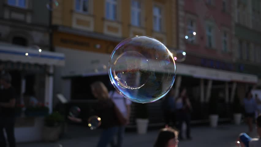 Slow motion fly and burst of a big soap bubble in a city center public place in Wroclaw Poland   Shutterstock HD Video #1011507926