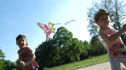 Children have fun running with a kite in park when it falls on a ground