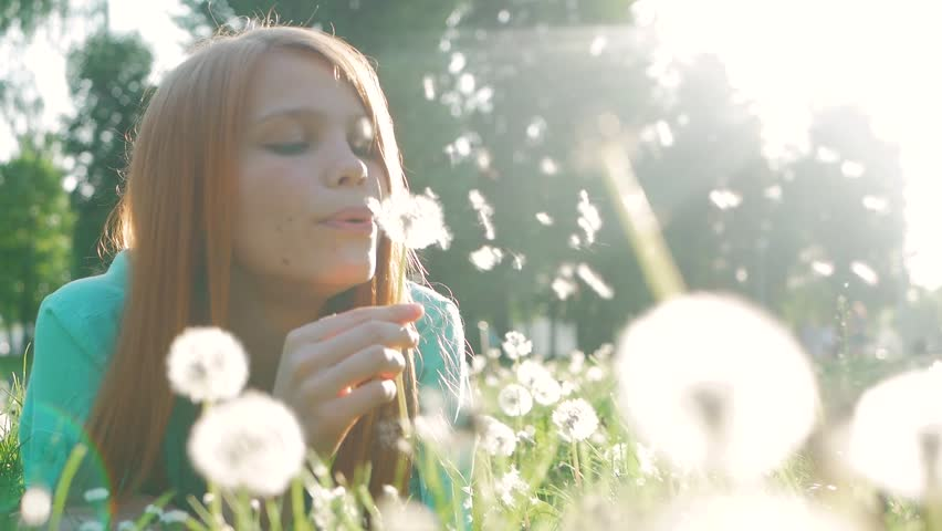 Beauty Young Woman with red hair Blowing Dandelion Wishing Joy Concept